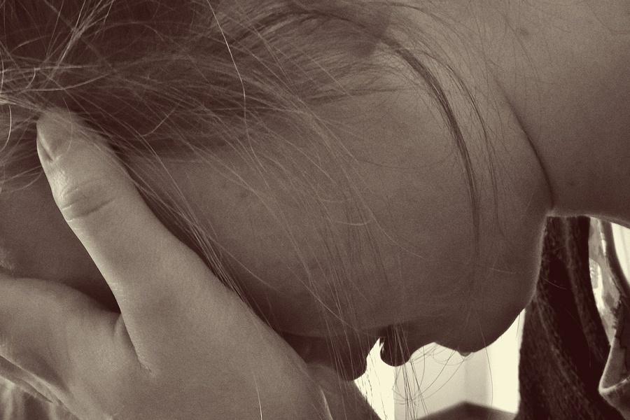 Eine junge Frau hält die Hand vors Gesicht und ist sichtlich krank. Fehlen ihr Mineralstoffe?