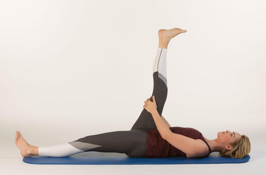 Mit der Beinstreckung-Rückenübung dehnt eine Frau die hintere Oberschenkelmuskulatur