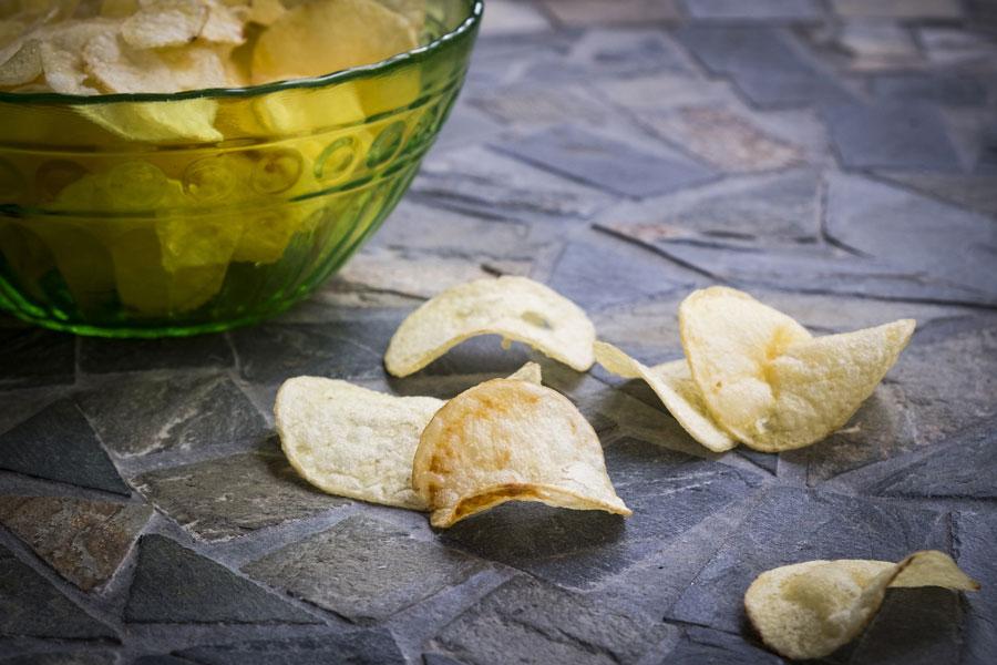 Kartoffelchips liegen in einer Schüssel und vereinzelt auf dem Tisch