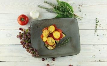 Tumbet - Mallorquinisches Kartoffelgericht serviert auf einem dunklen Teller