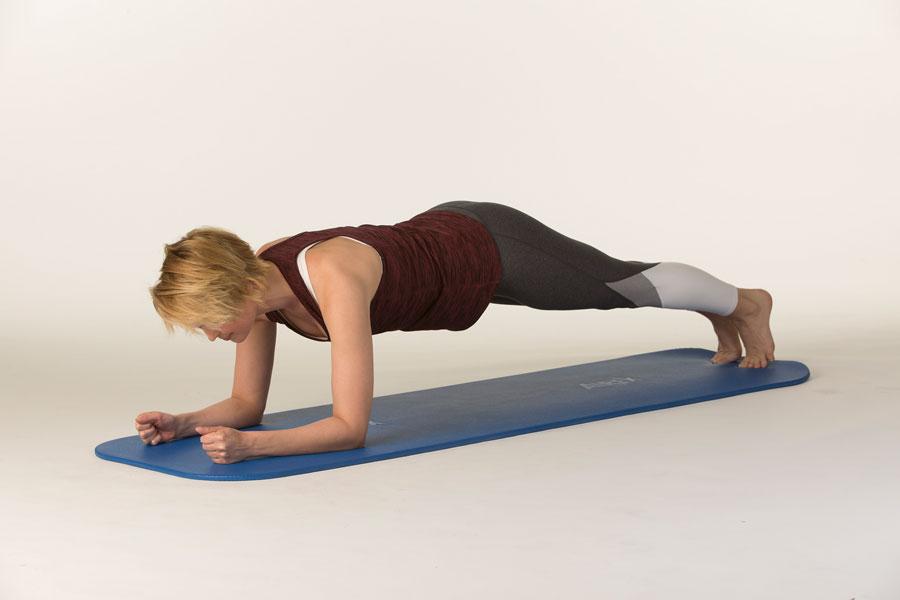 Ein Frau stärkt mit dieser Unterarmstützübung den ganzen Körper und stärkt so ihren Rücken