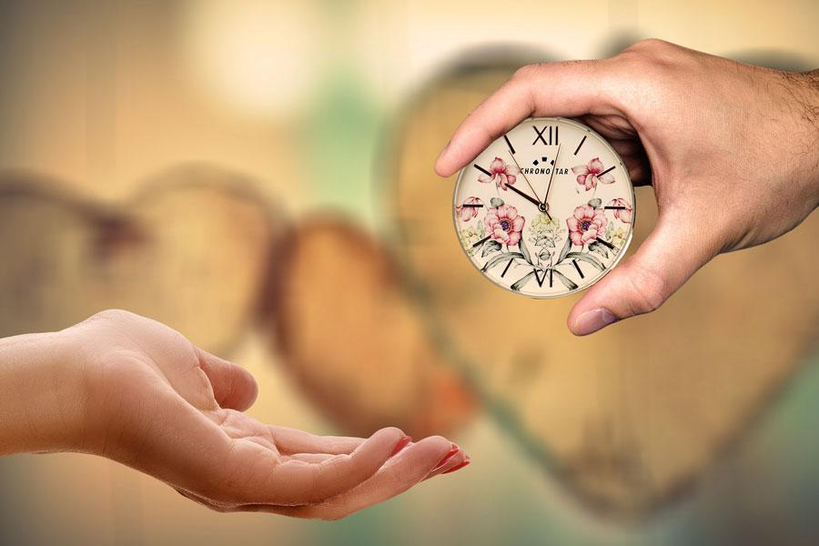 Eine Hand reicht der anderen eine Uhr als Symbolbild für Zeit und Gesundheit schenken