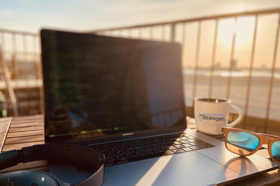 Arbeitsplatz im Freien mit Laptop und Kopfhörer