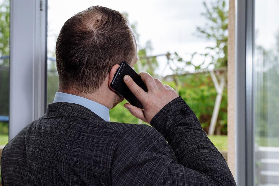 Eine Führungskraft telefoniert am offenen Fenster mit Blick aufs Grüne und erkundigt sich um das Befinder der Mitarbeiter