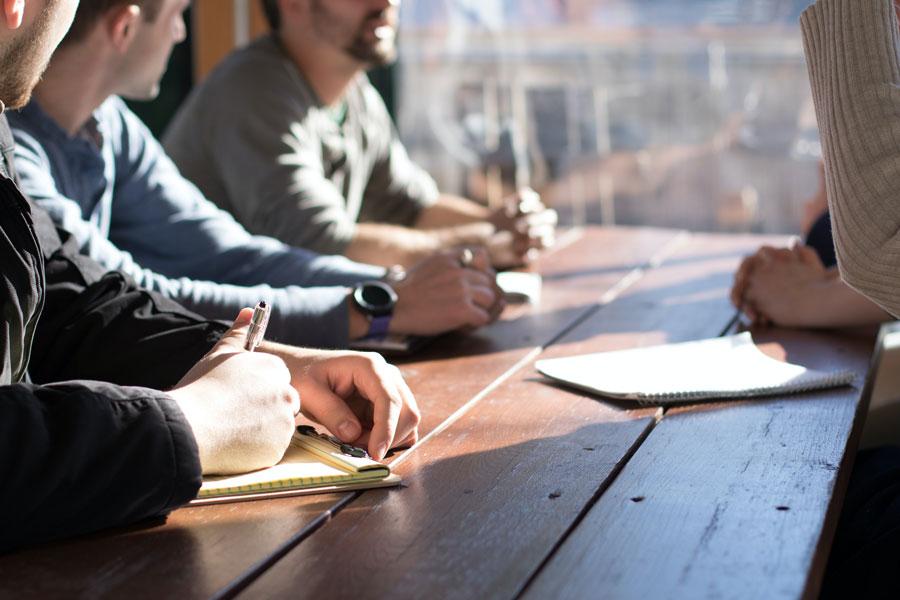 Eine Gruppe von Mitarbeitern an einem einfachen Holztisch als Zeichen des Wandels der Führung