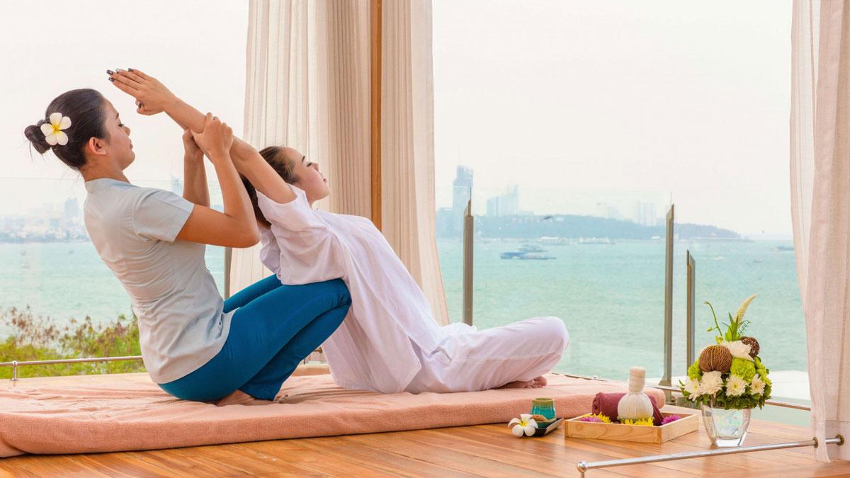 Eine Therapeutin wendet die Thai-Massage an