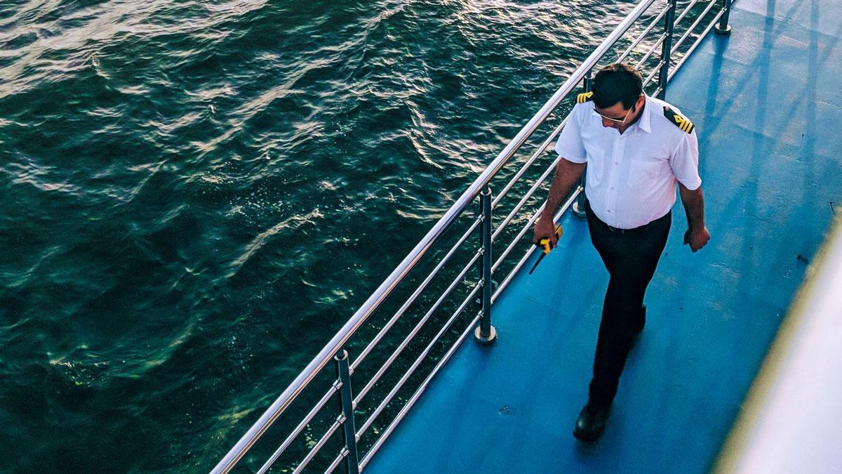 Ein Schiffsoffizier geht an der Reling entlang.