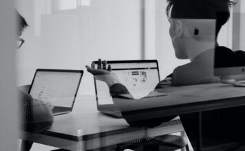 zwei junge Männer dikutieren in einem Meetingraum über die Arbeitswelt