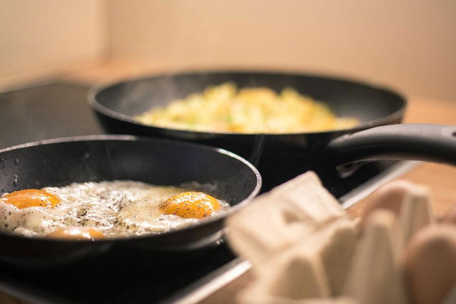 Rösti mit Spiegeleiern auf dem Herd für das Frühstück