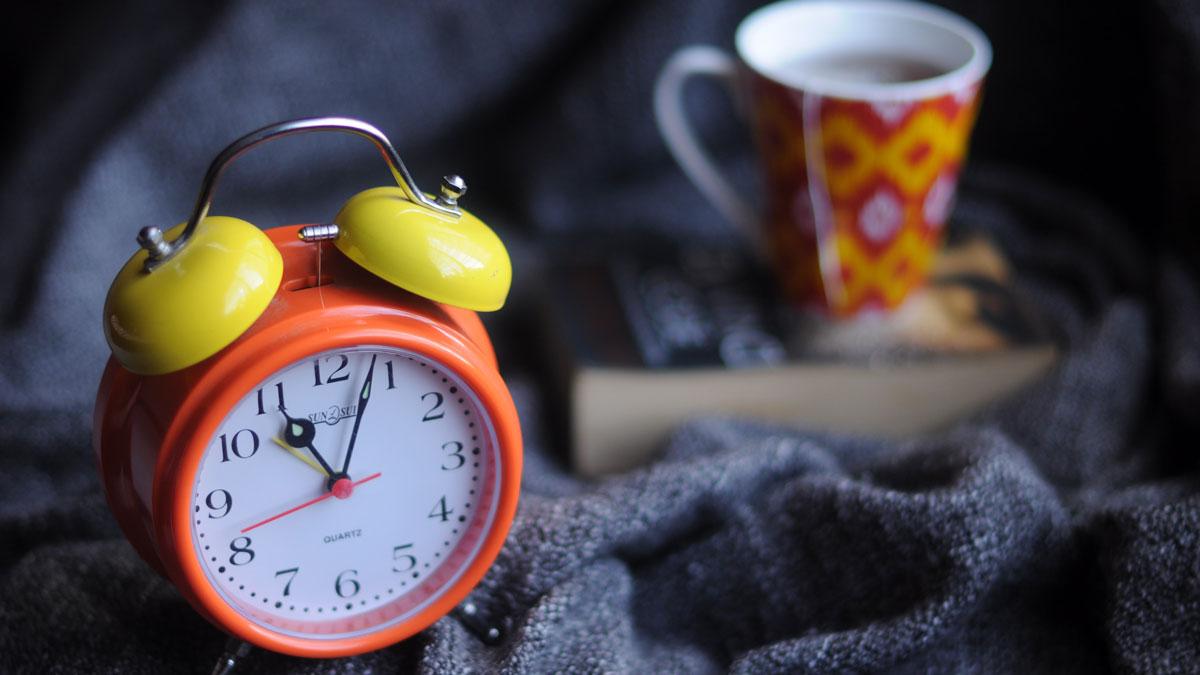 Ein Wecker und ein Tee auf einer dunklen Decke symbolisiert Intervallfasten 16/8