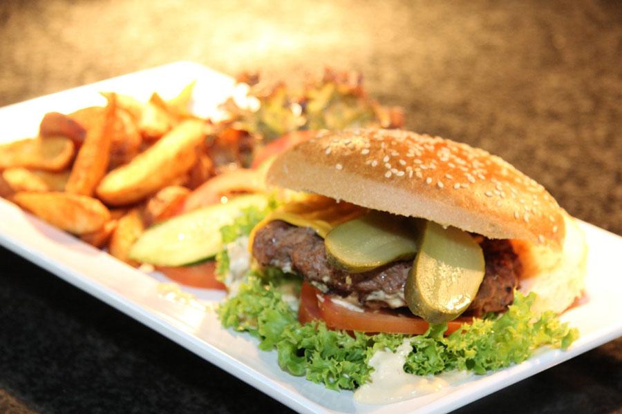 Hamburger mit Pommes auf einem weissen Teller kann auch zum Intervallfasten 16/8 gehören