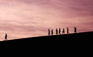 Eine Menschengruppe am Horizont die von einem Leader angeführt werden
