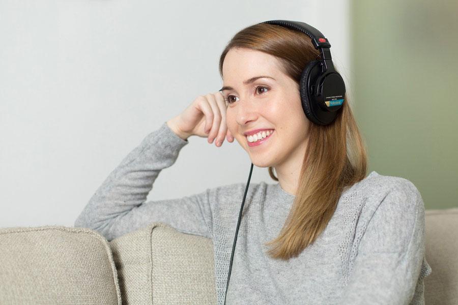 Eine junge Frau sitzt mit Kopfhörern entspannt auf der Coach