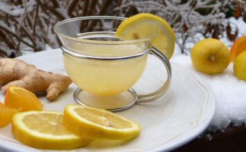 Zitronentee und Ingwer auf einem Teller, der auf einem schneebedeckten Tisch steht