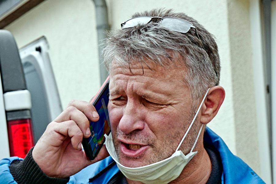 Ein Mann telefoniert mit heruntergezogener Maske