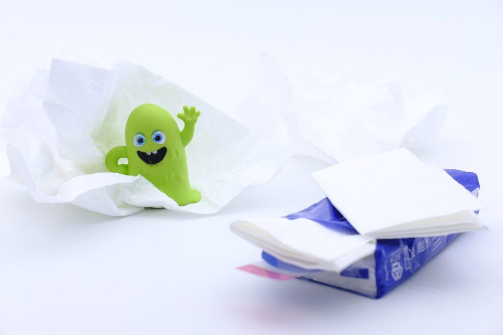Taschentuch und ein Plastik-Virus als Symbol für ein geschwächtes Immunsystem