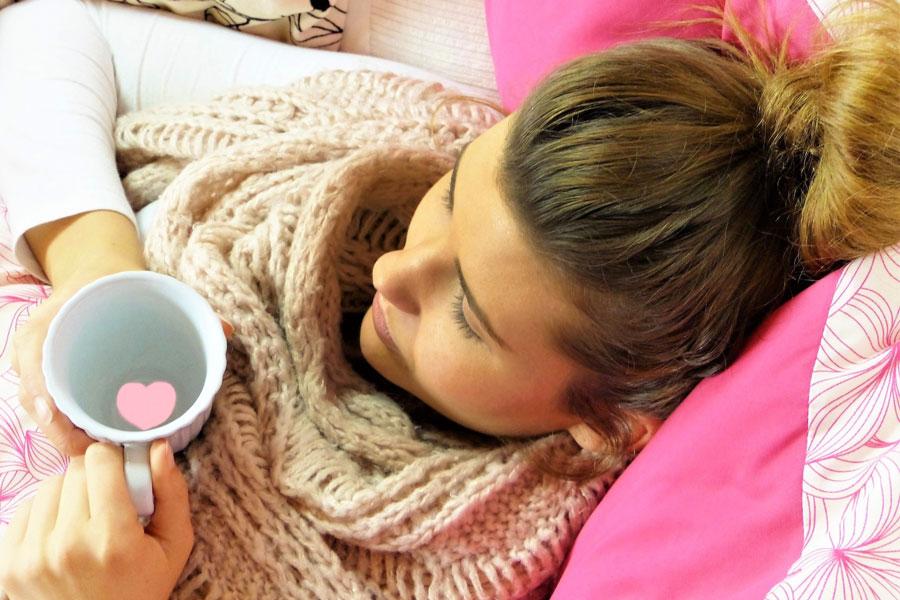 Eine junge Frau mit geschwächtem Immunsystem trinkt Tee