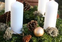 Ein Adventskranz mit Tannenzweigen und vier weissen Kerzen