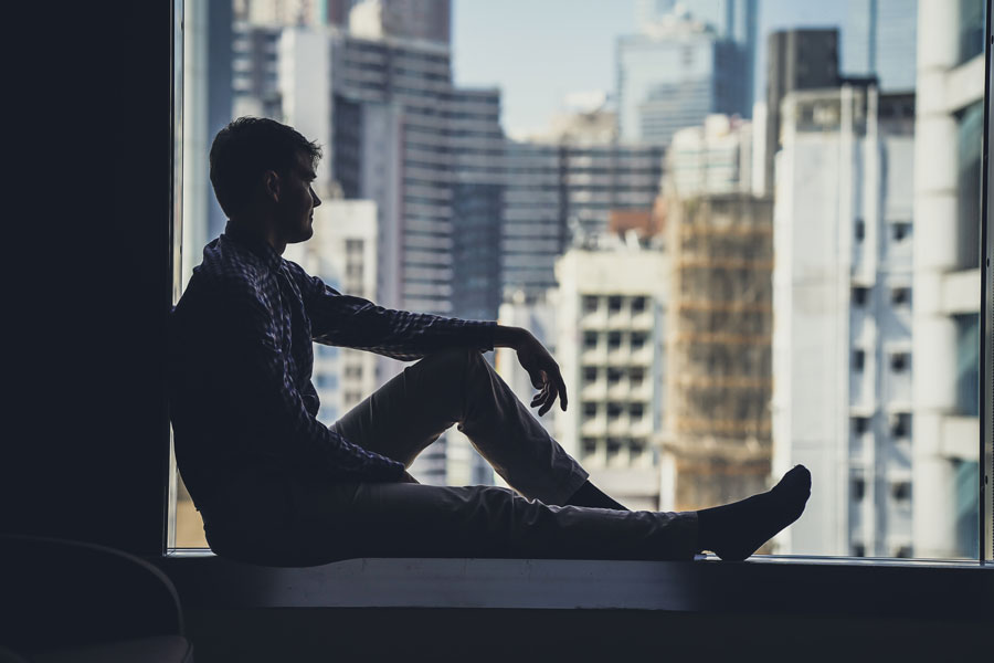 Ein Mann sitzt auf der Fensterbank und vermisst die Kommunikation im Team