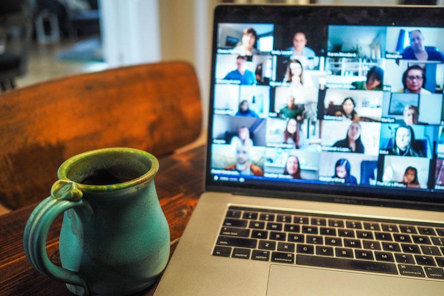 Laptop im Home Office, auf dem ein Online Meeting stattfindet.