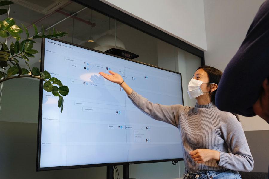 Eine Mitarbeiterin macht mit Maske eine Präsentation im Unternehmen