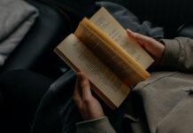 Eine Frau liest auf Grund von Buchempfehlungen im Bett ein Buch