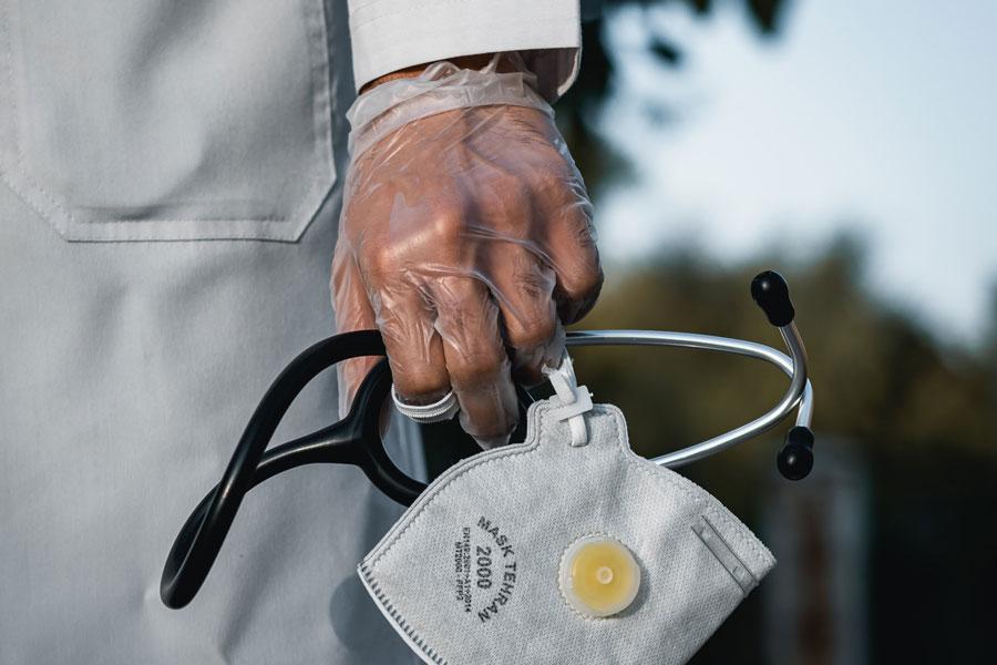 Ein Arzt mit Schutzmaske in der Hand