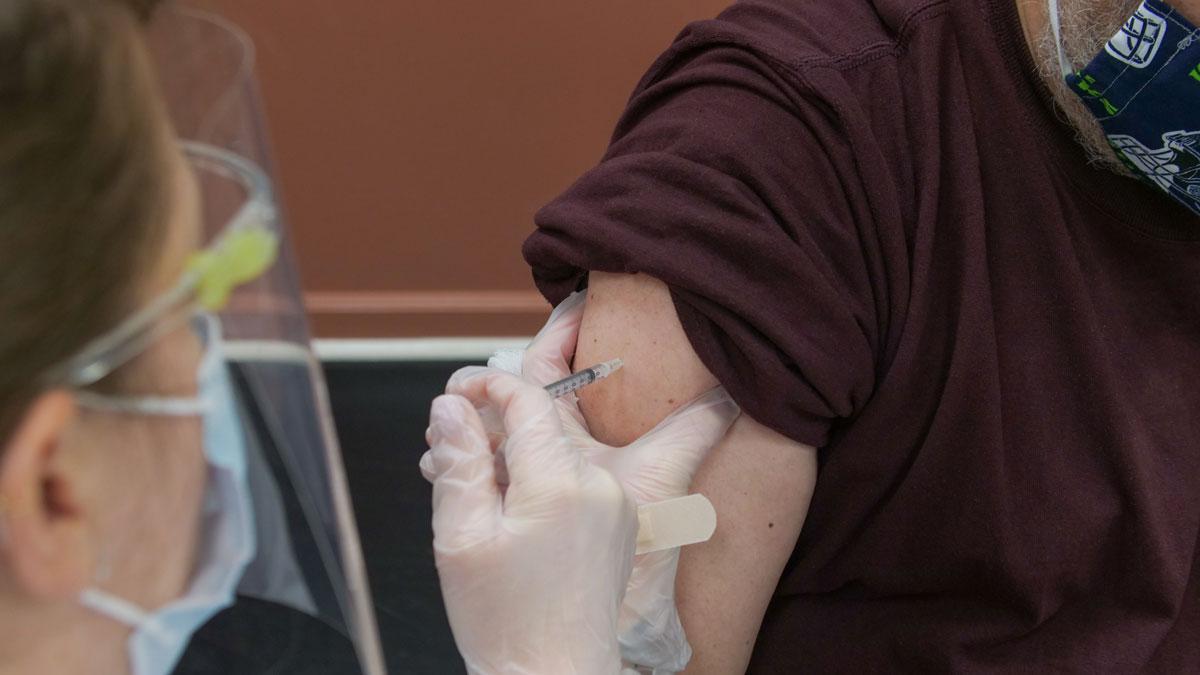 Ein Ärztin verabreicht einem Mann eine Impfung