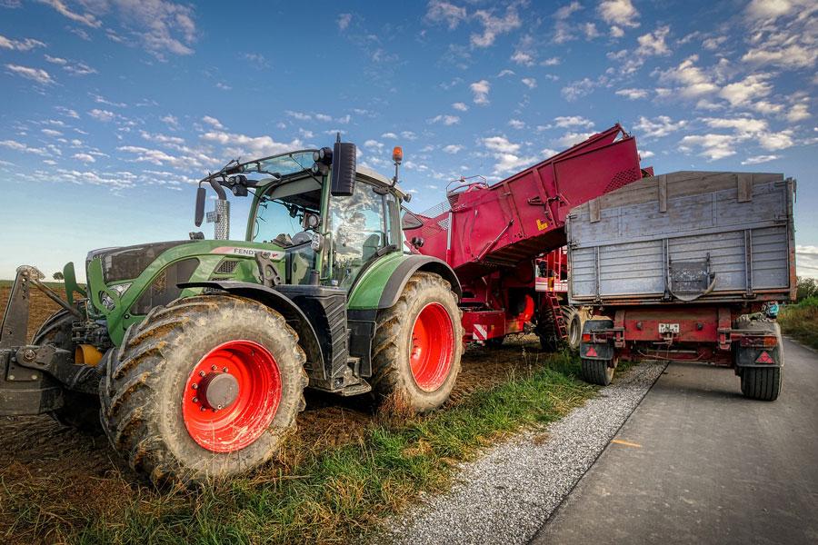 Ein Traktor auf dem Feld erntet Frischkartoffeln