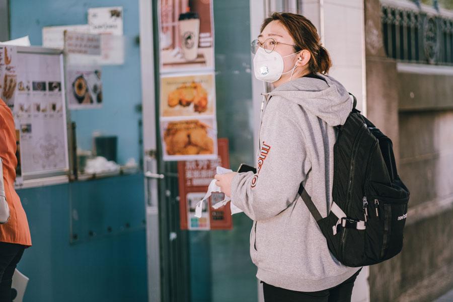 Eine junge Frau betritt mit Schutzmaske eine Takeaway-Geschäft