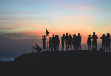 Eine Gruppe von Menschen beobachten den Sonnenaufgang.