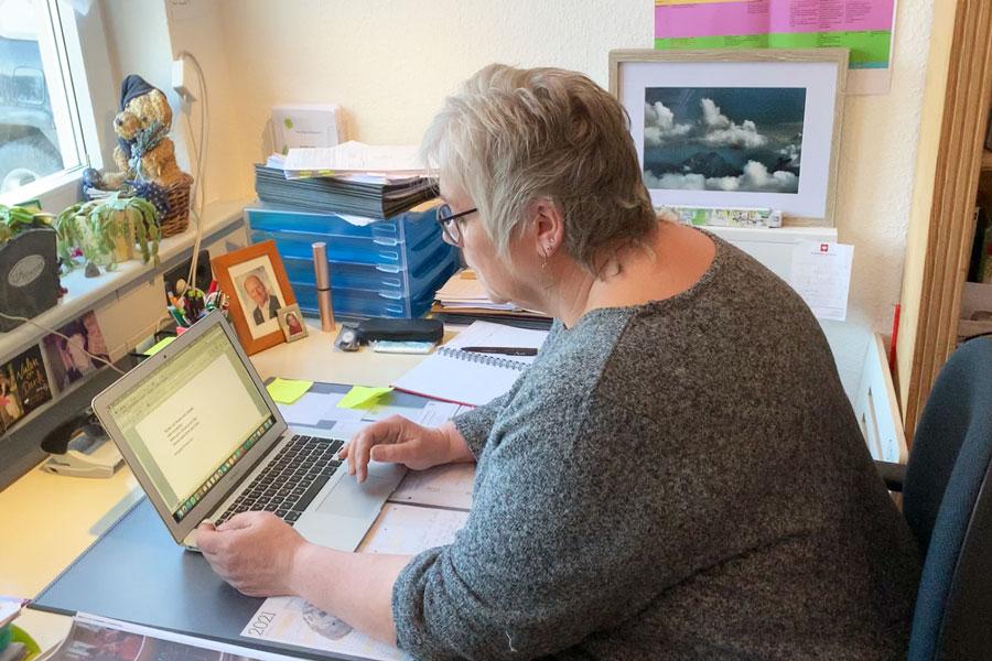 Heike sitzt am Schreibtisch und wünscht sich ein Steharbeitsplatz