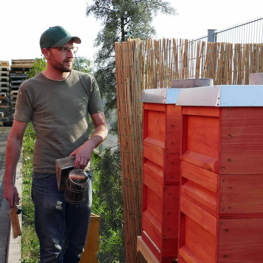 Ein Imker betreut seine Bienenvölker, die durch Bienenpatenschaft finanziert wird