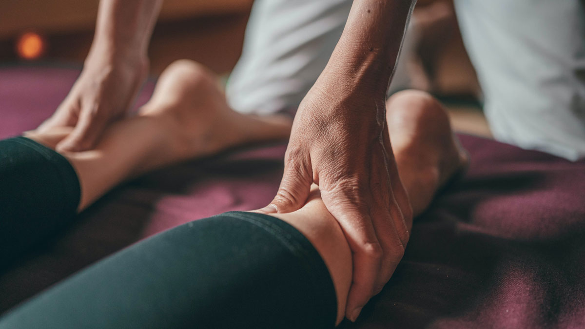 Therapeut massiert schwere Beine