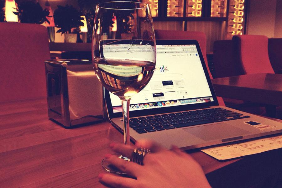 Entspanntes Atmen mit Laptop und Glas Wein bei der virtuellen Buchvorstellung