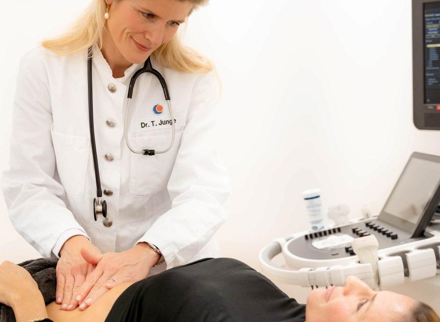 Check-up: Eine Ärztin tastet bei einer Untersuchung den Bauch einer Patientin ab.