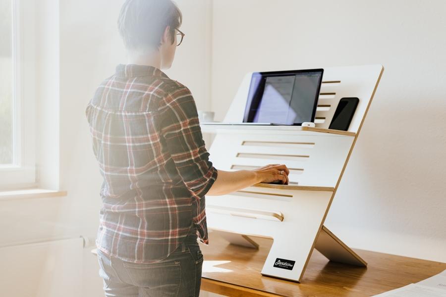 Eine Frau arbeitet mit Hilfe eines mobilen Schreibtisch-Aufsatzes im Stehen am Laptop.
