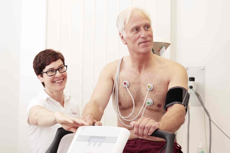 Ein Mann sitzt auf einem Ergometer. Eine Ärztin überwacht die Messung der Werte.