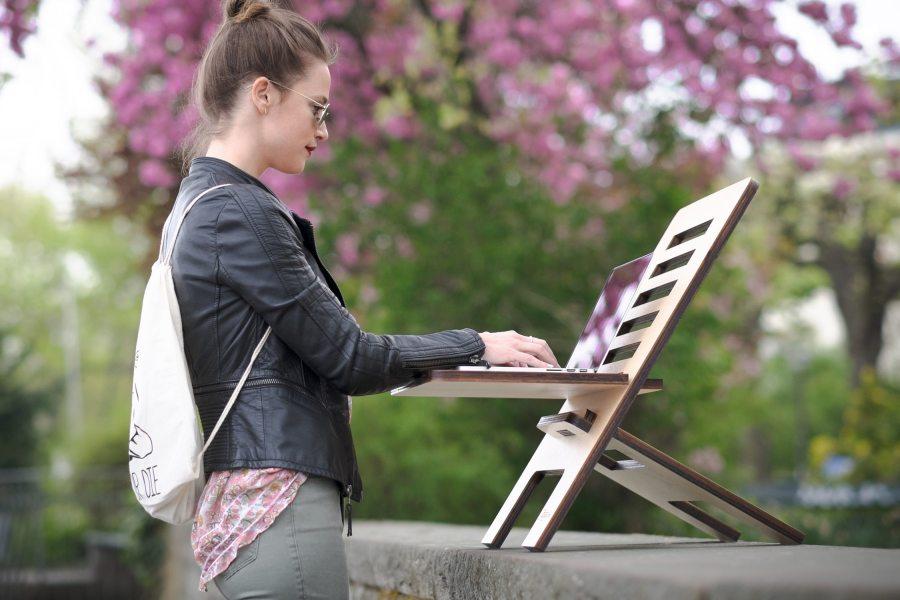 Eine junge Frau arbeitet an einem Laptop  mit Hilfe eines mobilen Schreibtischaufsatzes. Dieser steht auf einer Mauer im Freien.