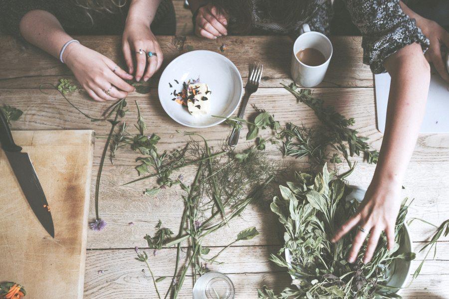 Zwei Personen sitzen an einem Tisch und zerkleinern selbst gepflückte Kräuter.