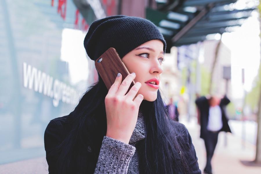 Eine junge Frau telefoniert auf der Straße mit ihrem Smartphone.