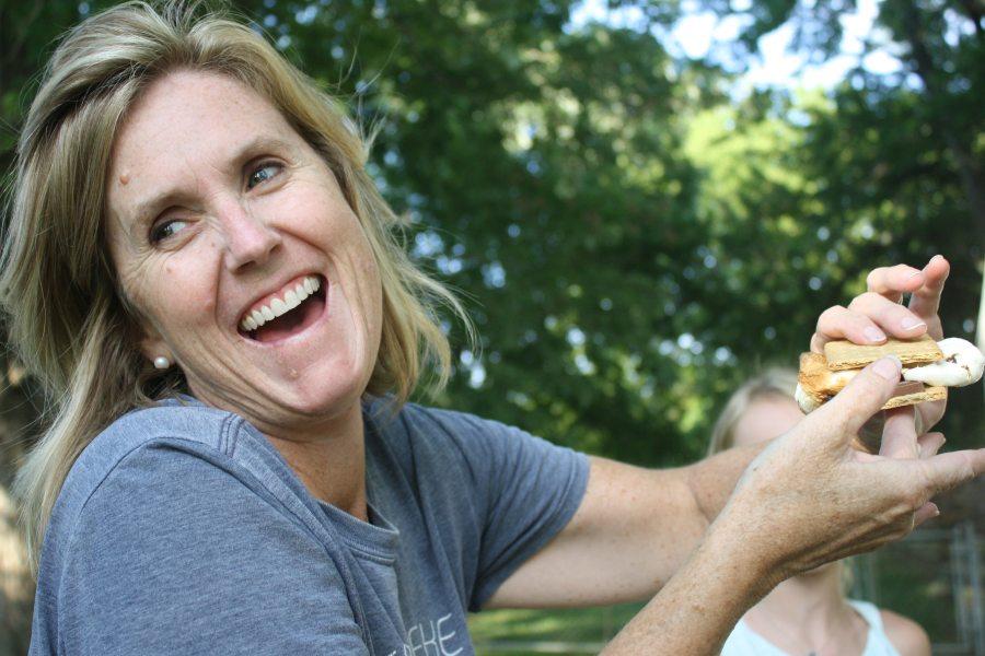 Gesund schön: Lachende Frau im Garten mit einem Sandwich in der Hand.