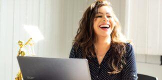 Junge Frau sitzt lachend am Laptop