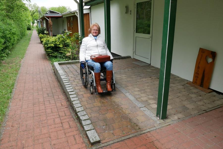 Frau im Rollstuhl vor einer barrierefreien Ferienwohnung