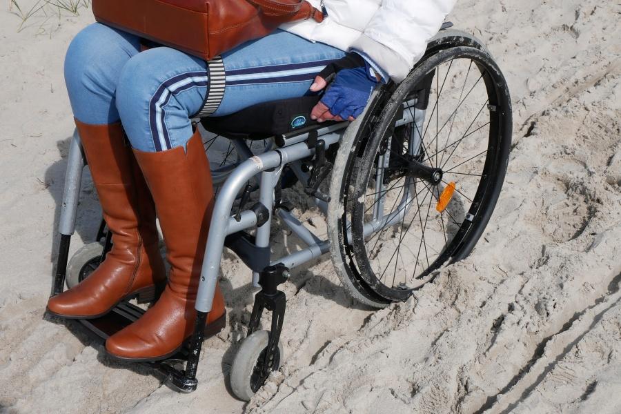 Frau steckt mit Rollstuhl im Sand fest