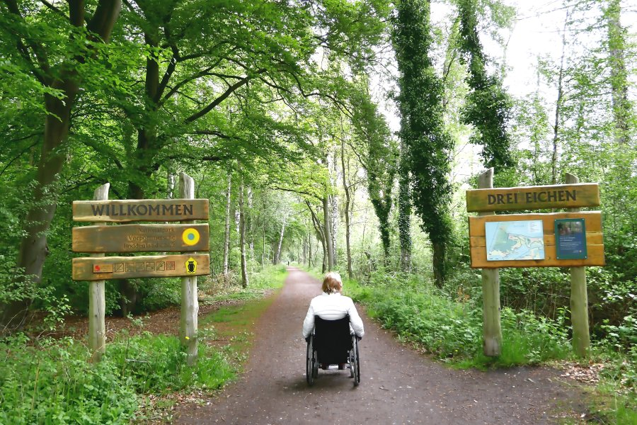 Frau mit Rollstuhl am Eingang zum Nationalpark