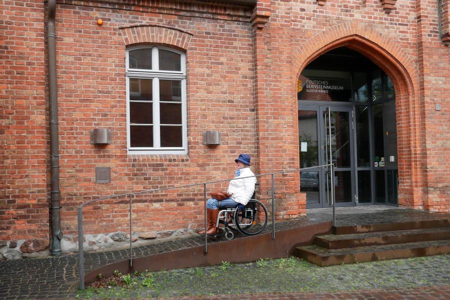 Rollstuhlfahrerin auf der Rampe am Eingang zum Bernsteinmuseum in Ribnitz-Dammgarten Mitte