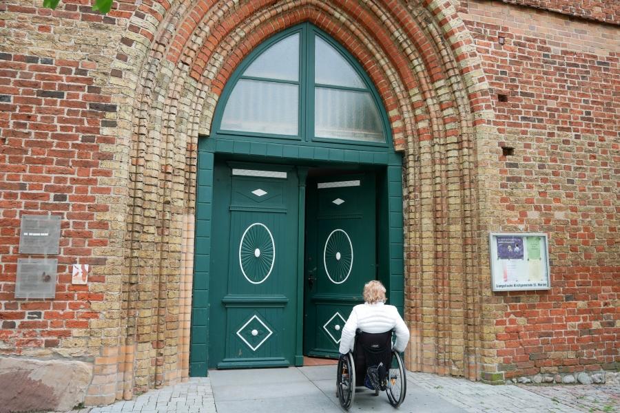 Rollstuhlfahrerin am Eingang zur Marienkirche in Ribnitz-Dammgarten Mitte