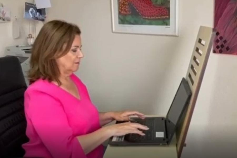 Eine Frau arbeitet an ihrem Laptop, der auf einem mobilen Schreibtischaufsatz steht