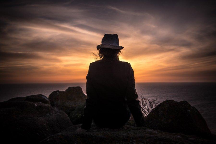 Eine Person sitzt auf einem Felsen und schaut in der Dämmerung aufs Meer